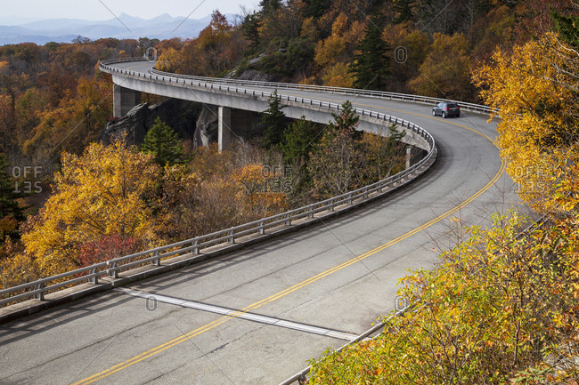 Car driving on the Linn Cove Viaduct along the Blue Ridge Parkway in Autumn