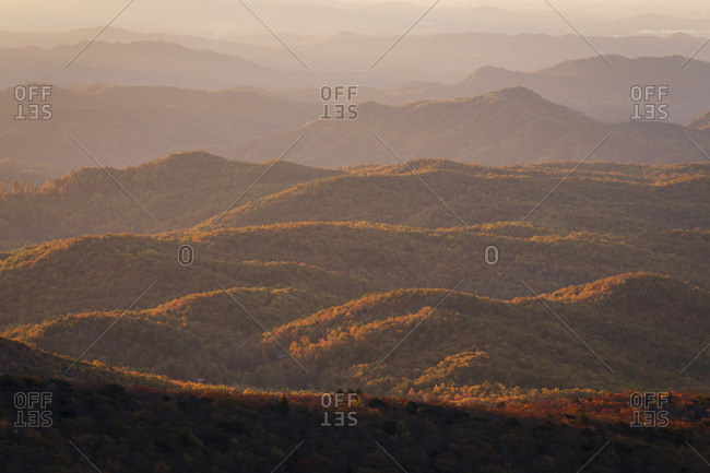 Rolling foothills of the Blue Ridge Mountains as the tops are lit with golden sunrise light in Western, North Carolina