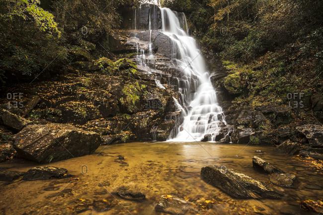 Long exposure of waterfall surrounded by fall colors at Eastatoe Falls outside of Rosman, North Carolina