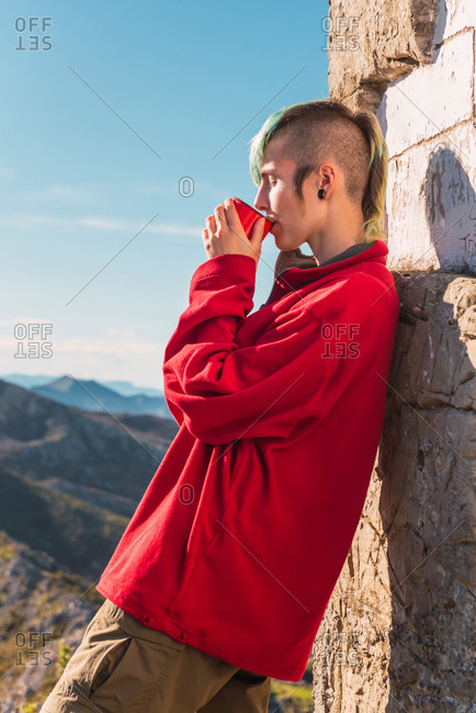 Side view of androgynous traveler standing in highlands on sunny day and enjoying hot drink during trip in El Mazuco with eyes closed