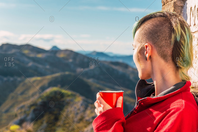 Side view of androgynous traveler standing in highlands on sunny day and enjoying hot drink during trip in El Mazuco looking away