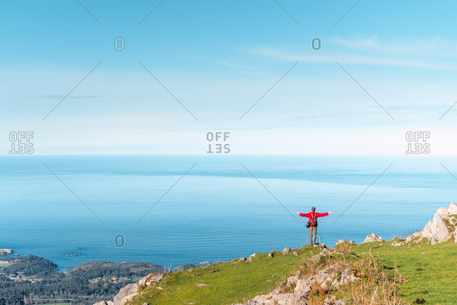 Back view of unrecognizable hiker standing with outstretched arms on edge of cliff and enjoying freedom during adventure in El Mazuco