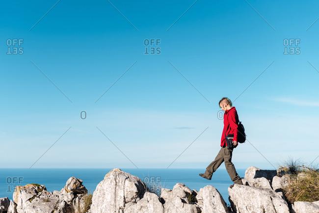 Side view of female hiker walking on rocks while trekking in highland terrain against blue sky in El Mazuco