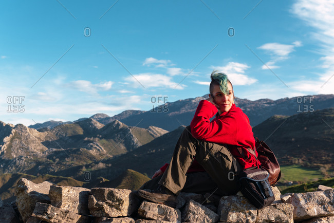 Side view of tranquil explorer sitting on rocks on trail while having break during hiking in highlands in El Mazuco and looking away