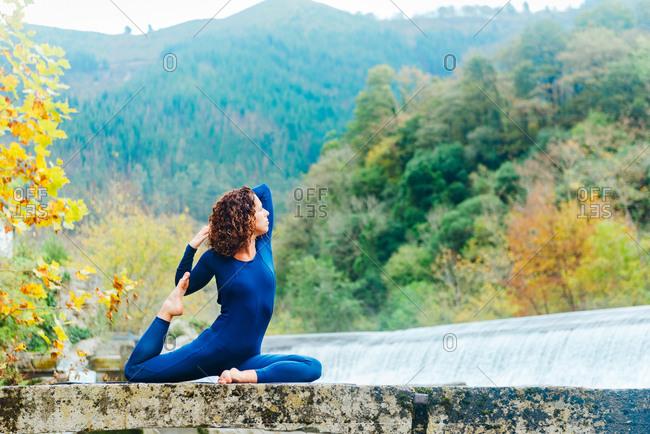 Side view of serene female sitting in Eka Pada Rajakapotasana on stone near waterfall and practicing yoga while stretching body