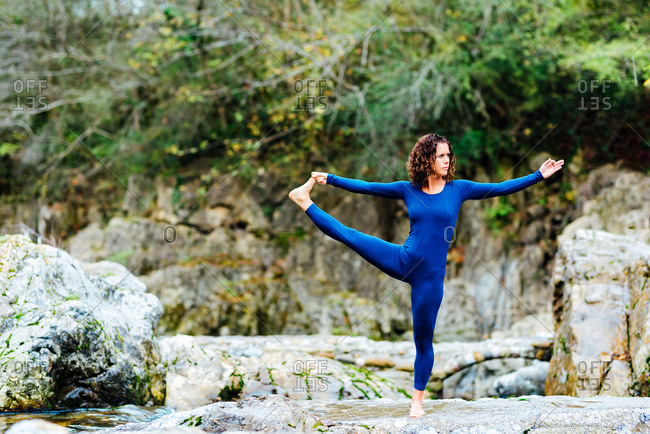 Female balancing on mat in Hasta Padangusthasana and practicing mindfulness near waterfall in nature