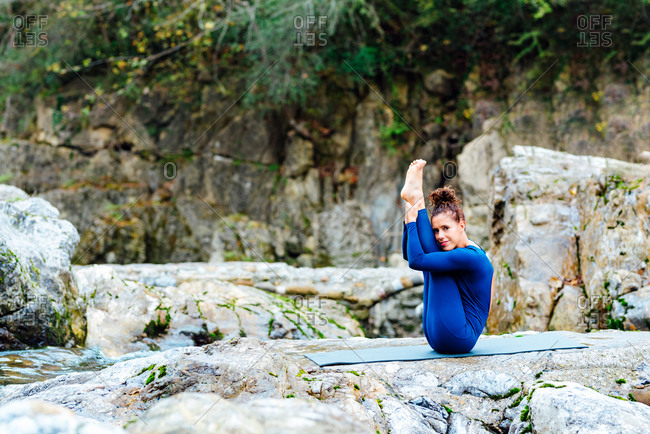 Side view of graceful female sitting on mat in Urdhva Mukha Pascimottanasana and looking at camera while doing yoga in rocky forest