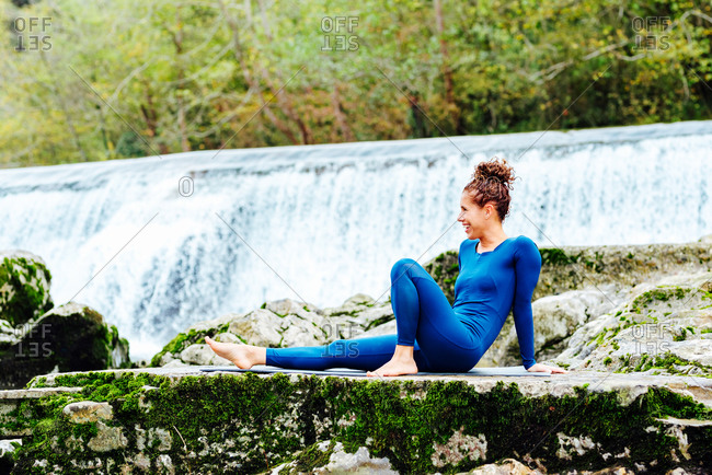 Positive female in sportswear sitting on mat while practicing yoga on shore of lake and looking away
