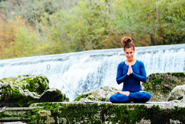 Content female sitting in Padmasana with Namaste gesture while doing yoga and looking at camera