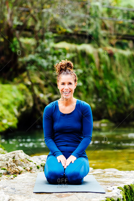 Positive female in sportswear sitting on mat in Vajrasana while practicing yoga on shore of lake and looking at camera