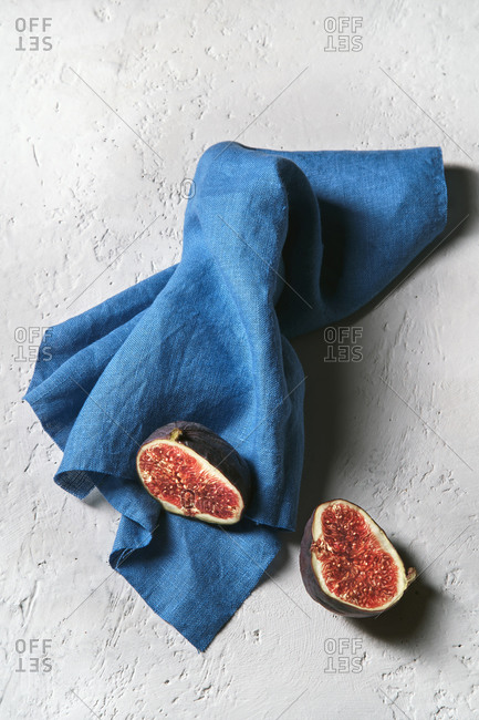 From above of halves of fresh sweet fig placed on napkin on white desk
