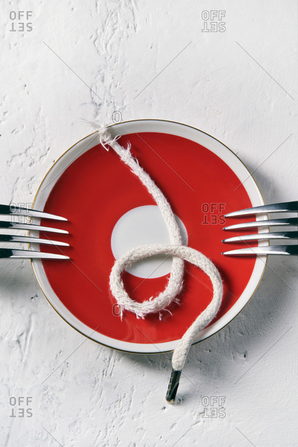 Top view of plate with old torn shoelace placed on table with fork showing concept of poverty and hunger