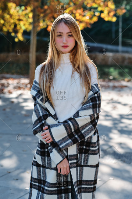 Young female dressed in trendy checkered coat and white turtleneck with jeans standing in park in sunny autumn day looking at camera