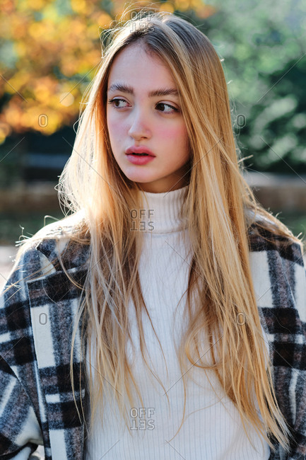 Young female dressed in trendy checkered coat and white turtleneck with jeans standing in park in sunny autumn day looking away