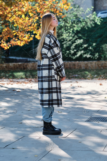 Full body side view of young female dressed in trendy checkered coat and white turtleneck with jeans standing in park in sunny autumn day looking away