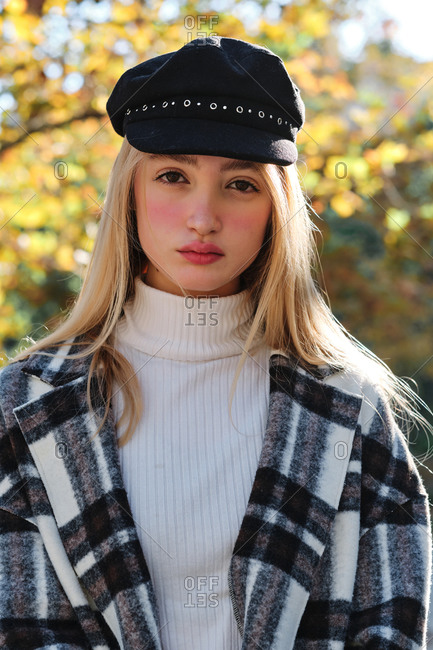 Side view of tranquil young long haired blonde female in stylish hat and checkered coat enjoying sunny weather standing looking at camera in autumn park