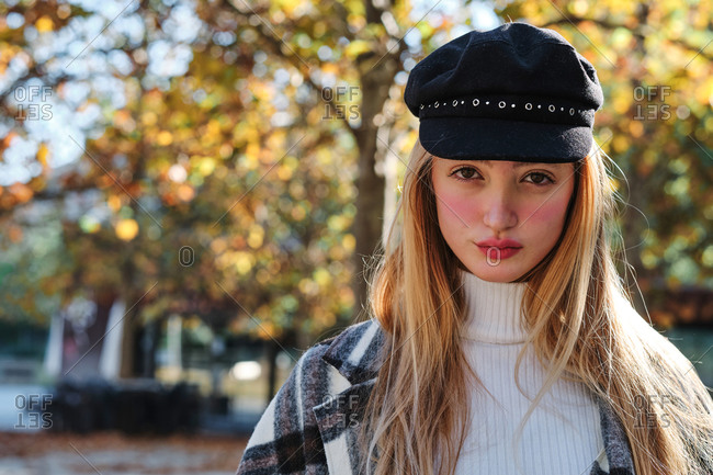 Tranquil young long haired blonde female in stylish hat and checkered coat enjoying sunny weather standing looking at camera in autumn park