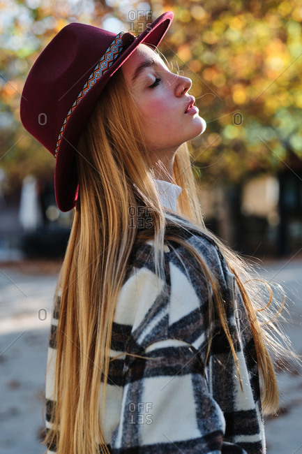 Side view of tranquil young long haired blonde female in stylish hat and checkered coat enjoying sunny weather standing with eyes closed in autumn park