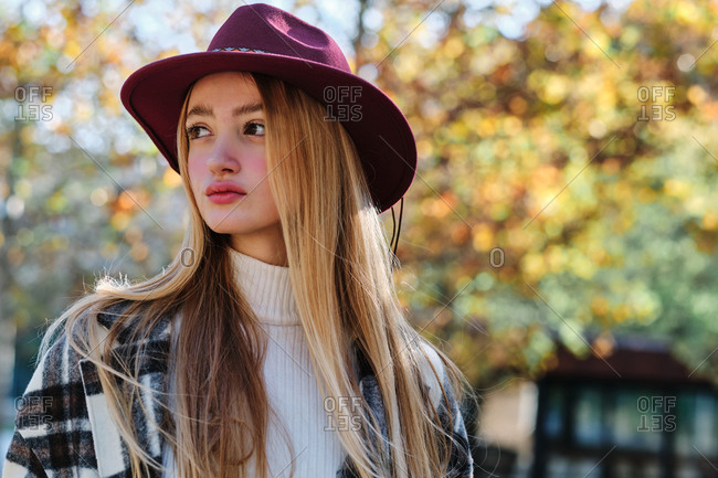Tranquil young long haired blonde female in stylish hat and checkered coat enjoying sunny weather standing looking away in autumn park