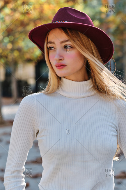 Attractive teen blonde female in turtleneck sweater and stylish cap looking away while standing against blurred background of autumn trees in park