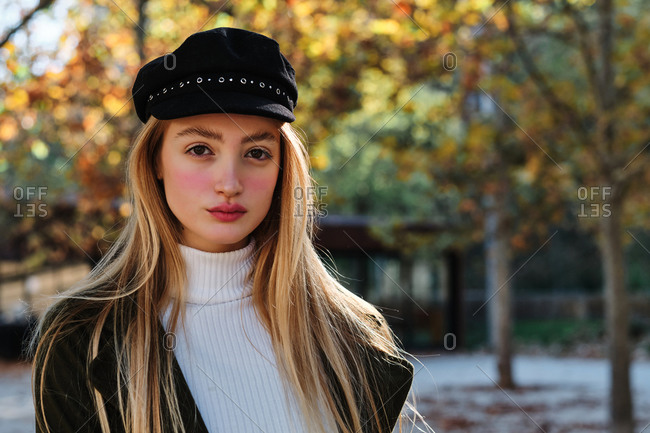 Attractive teen blonde female in turtleneck sweater and stylish cap looking at camera while standing against blurred background of autumn trees in park