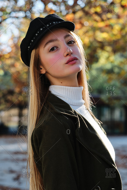 Side view of attractive teen blonde female in turtleneck sweater and stylish cap looking at camera while standing against blurred background of autumn trees in park