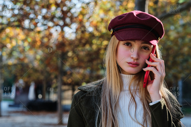 Serious millennial female in trendy outfit and hat chatting with red smartphone while standing in autumn park looking at camera