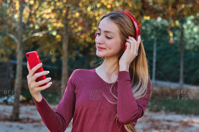 Positive young female student using bright red mobile phone and wireless headphones during video call while spending autumn day in park