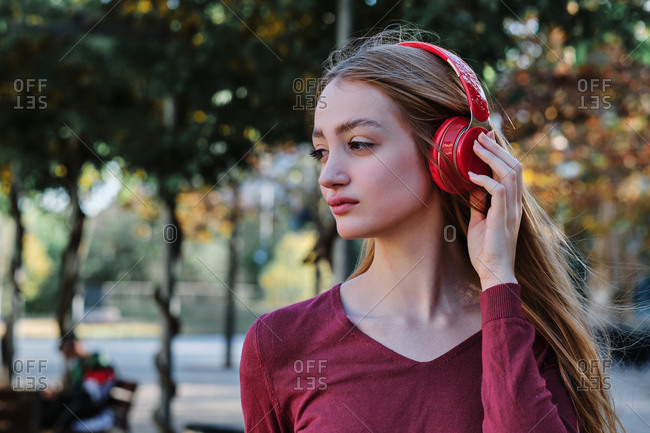 Thoughtful sad young female student using bright red wireless headphones while spending autumn day in park