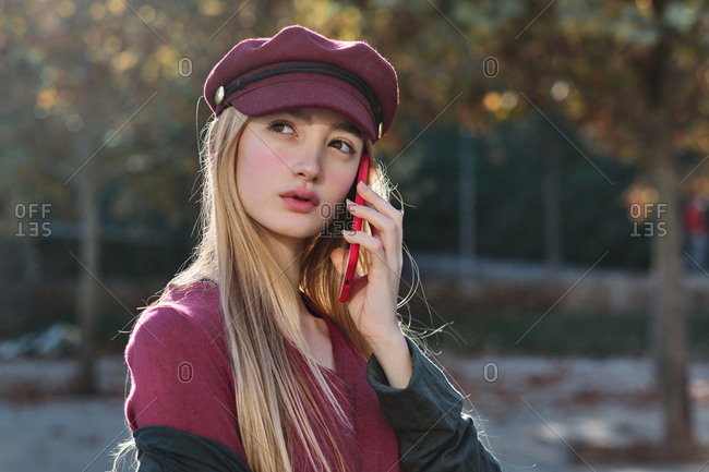 Serious millennial female in trendy outfit and hat chatting with red smartphone while standing in autumn park looking away