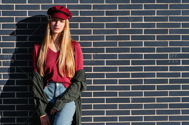 Stylish modern young blonde female in trendy autumn outfit with red cap and coat standing in sunlight against black brick wall
