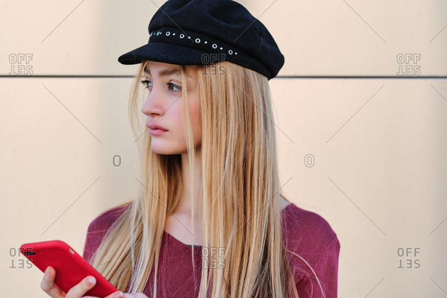 Serious teen female student in trendy autumn outfit and hat browsing red mobile phone while standing near beige wall looking away