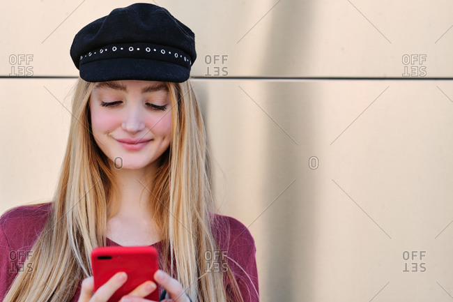 Smiling teen female student in trendy autumn outfit and hat browsing red mobile phone while standing near beige wall