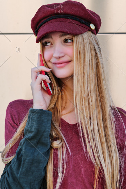 Smiling teen female student in trendy autumn outfit and hat browsing red mobile phone while standing near beige wall looking away