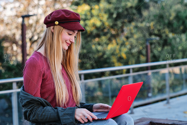 Focused millennial female in trendy casual clothes and cap sitting on wooden bench and browsing modern red laptop while spending autumn day in park