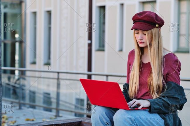 Positive millennial female student in trendy autumn outfit and hat browsing red laptop while sitting on paved terrace on city street