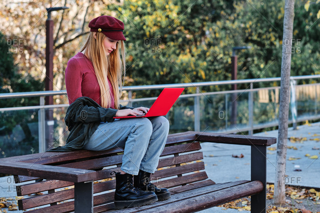 Full body of focused millennial female in trendy casual clothes and cap sitting on wooden bench and browsing modern red laptop while spending autumn day in park