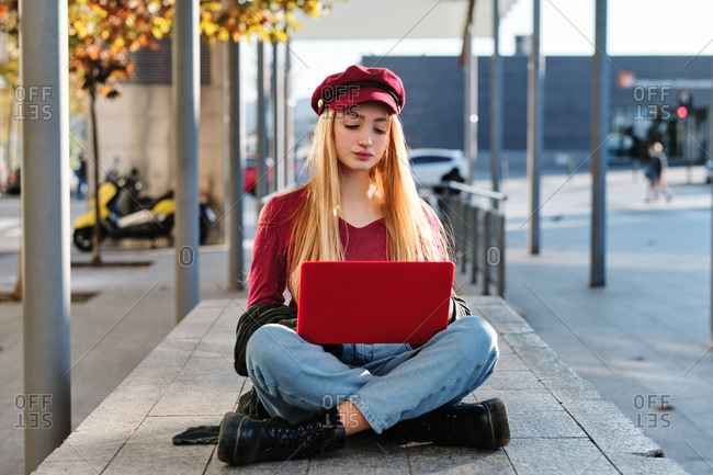 Positive millennial female student in trendy autumn outfit and hat browsing red laptop while sitting with legs crossed on paved terrace on city street