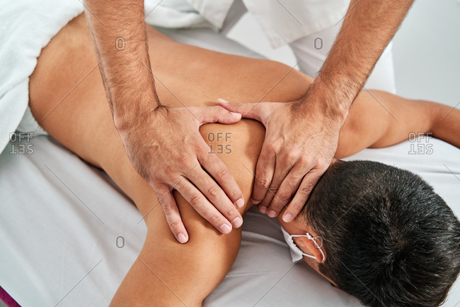 High angle of crop male osteopath massaging shoulder of client lying on table in clinic during rehabilitation session