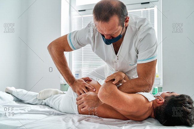 Focused male physiotherapist massaging back of patient lying on table during osteopathy session