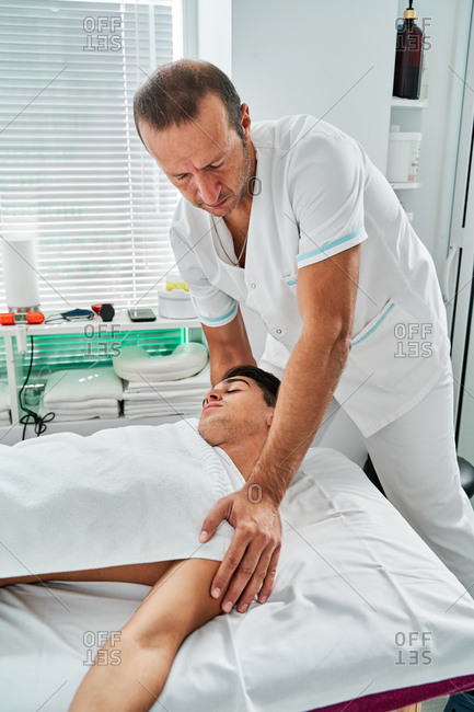 High angle of osteopath treating neck of male patient lying on table in medical room during rehabilitation procedure