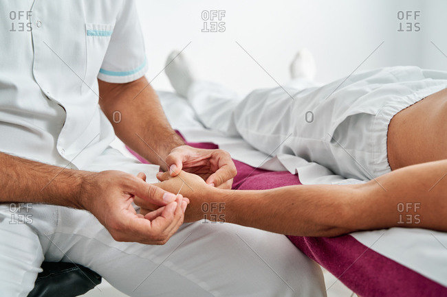 High angle of male physiotherapist using needle on hand of client during acupuncture therapy in clinic