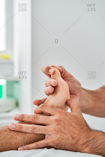 Concentrated male therapist massaging feet of patient lying on medical table in clinic during osteopathy session