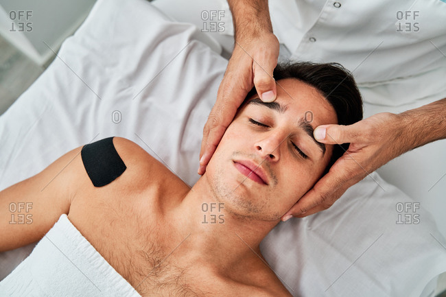 Top view of crop male osteopath massaging face of calm patient lying with closed eyes in medical room during physiotherapy treatment