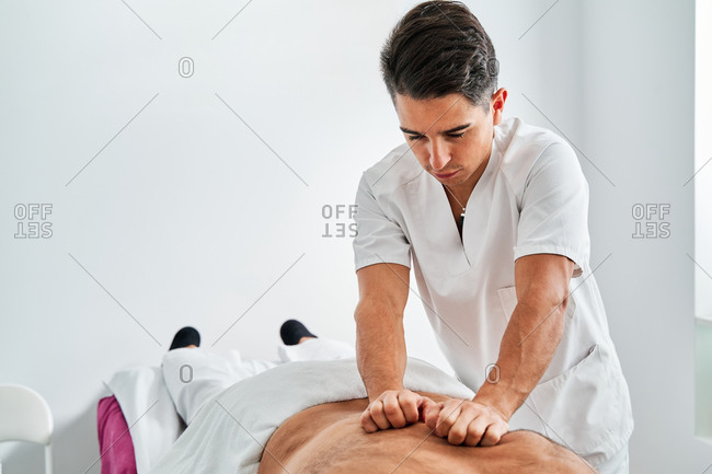 Physiotherapist massaging back of patient lying on medical table during rehabilitation process in clinic