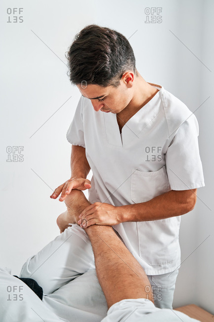 Focused male osteopath massaging feet of client during rehabilitation session in bright medical room of clinic