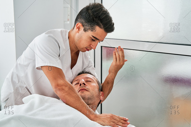 Osteopath treating neck of male patient lying on table in medical room during rehabilitation procedure