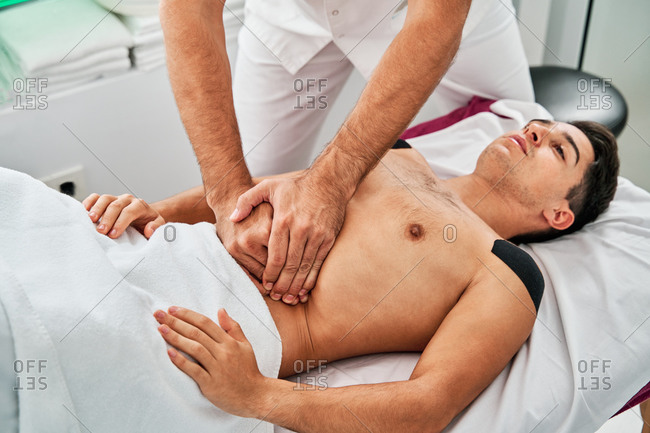 High angle of male patient getting massage of stomach during osteopathy session in modern clinic