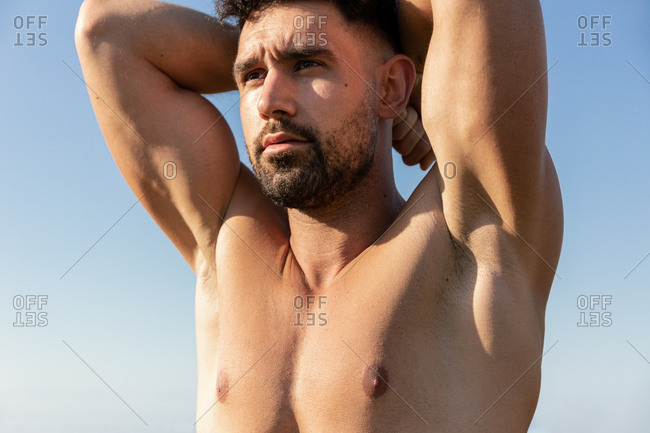 Shirtless bearded male athlete with strong body standing with raised arms on background of blue sky and looking away