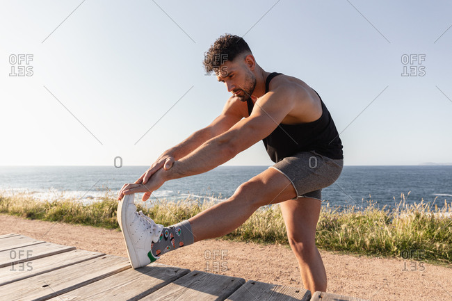 Side view of muscular male doing forward bends and warming up before workout while standing near promenade on seashore